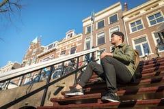 Hombre asiático urbano con la mochila que se sienta en las escaleras Apuesto C Imagen de archivo