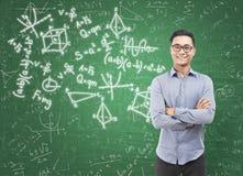 Hombre asiático y fórmulas en la pizarra Imagen de archivo
