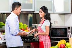 Hombre asiático y mujer que cocinan junto Imagenes de archivo