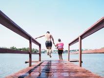 Hombre asiático y su hermana que saltan del puente de madera Imágenes de archivo libres de regalías