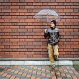 Hombre asiático en una chaqueta de Brown con un paraguas claro Imagenes de archivo