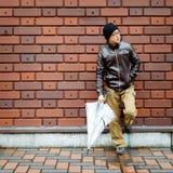 Hombre asiático en una chaqueta de Brown con un paraguas claro Imagen de archivo