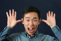 Hombre asiático joven divertido que hace la cara Imágenes de archivo libres de regalías