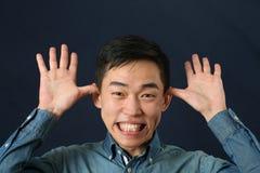 Hombre asiático joven divertido que hace la cara Fotografía de archivo libre de regalías