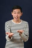Hombre asiático joven sonriente que gesticula con dos manos Imágenes de archivo libres de regalías