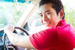 Hombre asiático que conduce el coche Imagenes de archivo