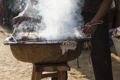 Hombre asiático que hace la barbacoa de la manera tradicional Foto de archivo