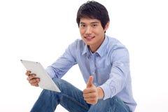 Hombre asiático que sostiene el ordenador de la tablilla aislado Imagen de archivo
