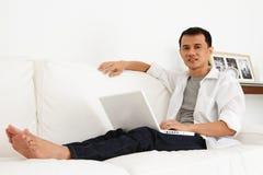 Hombre asiático que trabaja en la computadora portátil en el país Imagenes de archivo