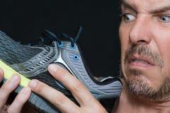 Hombre asqueado por el olor de los zapatos Imagen de archivo libre de regalías