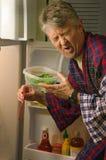 Hombre asqueado que huele la comida putrefacta estropeada Fotografía de archivo libre de regalías