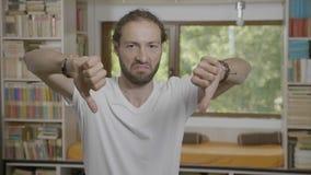 Hombre asqueado que tiene reacción negativa que muestra los pulgares abajo que desaprueban - almacen de video