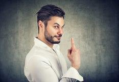 Hombre astuto elegante de las ventas que detiene el finger foto de archivo libre de regalías
