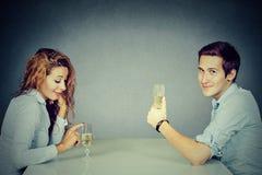 Hombre astuto y mujer escéptica que se sientan en el vino de consumición de la tabla imagenes de archivo