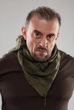 Hombre asustadizo adulto en una chaqueta del camuflaje una persona peligrosa Foto de archivo libre de regalías