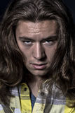 Hombre asustadizo con el pelo y los males de ojo largos Fotos de archivo