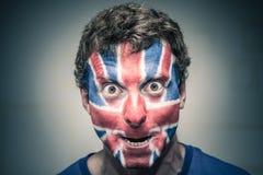 Hombre asustadizo con la bandera británica pintada en cara Foto de archivo