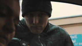 Hombre asustadizo del bandido que mira a la mujer que invita al teléfono móvil en coche almacen de video