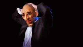 Hombre asustadizo en traje con la máscara que lleva a cabo su cabeza Imagen de archivo