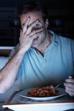 Hombre asustado que disfruta de la comida que ve la TV Foto de archivo libre de regalías