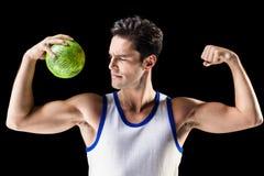 Hombre atlético confiado que sostiene la bola y que muestra los músculos Fotografía de archivo
