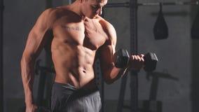 Hombre atlético de la aptitud que bombea para arriba los músculos con pesas de gimnasia en gimnasio interior almacen de metraje de vídeo