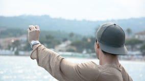 Hombre atlético en la playa que toma el selfie con la cámara de la acción almacen de video