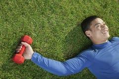 Hombre atlético feliz joven que se acuesta en hierba con la pesa de gimnasia roja, visión desde arriba Fotografía de archivo