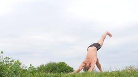 Hombre atlético flexible hermoso que hace asanas de la yoga en el parque almacen de video