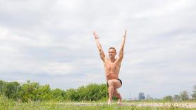 Hombre atlético flexible hermoso que hace asanas de la yoga en el parque almacen de metraje de vídeo