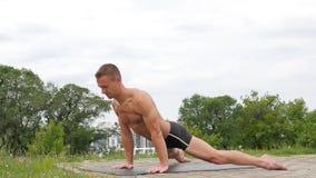 Hombre atlético flexible hermoso que hace asanas de la yoga en el parque metrajes