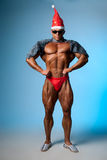 Hombre atlético fuerte en un sombrero de santa y vidrios oscuros Fotos de archivo