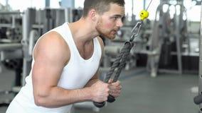 Hombre atlético fuerte en una camiseta en el entrenamiento del gimnasio en el dispositivo en modo bloque Entrenamiento de CrossFi fotos de archivo