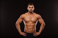 Hombre atlético fuerte - modelo de la aptitud que muestra su torso con seis ABS del paquete Aislado en fondo negro con Copyspace fotos de archivo