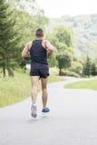 Hombre atlético fuerte que corre abajo del camino, concepto de li sano Fotos de archivo libres de regalías