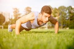 Hombre atlético fuerte que hace ejercicios en campo de deportes imagen de archivo