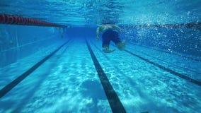 Hombre atlético fuerte que nada bajo el agua en piscina clara del balneario almacen de video
