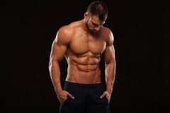 Hombre atlético fuerte - torso que muestra modelo de la aptitud con seis ABS del paquete los soportes derecho y ponen sus manos e Fotografía de archivo