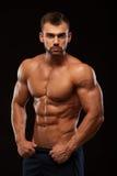 Hombre atlético fuerte - torso que muestra modelo de la aptitud con seis ABS del paquete los soportes derecho y ponen sus manos e Imagen de archivo libre de regalías