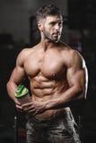 Hombre atlético hermoso de la aptitud que sostiene una coctelera y que presenta el gimnasio Imagen de archivo libre de regalías