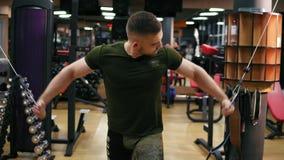 Hombre atlético hermoso que hace pectorals en el instructor de la cruce en el gimnasio Tirado en 4k almacen de video