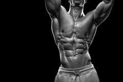 Hombre atlético hermoso que se resuelve con pesas de gimnasia Fotos de archivo libres de regalías