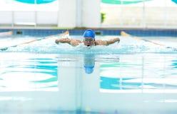Hombre atlético joven con técnica de la natación de la mariposa Fotos de archivo
