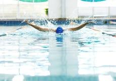 Hombre atlético joven con técnica de la natación de la mariposa Fotografía de archivo libre de regalías