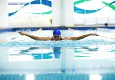 Hombre atlético joven con técnica de la natación de la mariposa Imagenes de archivo