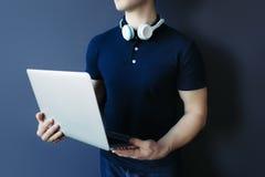 Hombre atlético joven en camiseta con los auriculares y el ordenador portátil Imagenes de archivo
