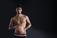 Hombre atlético joven en el fondo oscuro que sostiene la bola del baloncesto Foto de archivo libre de regalías