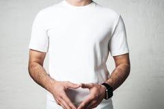 Hombre atlético joven en la camiseta blanca en blanco, primer del estudio, empt Foto de archivo libre de regalías
