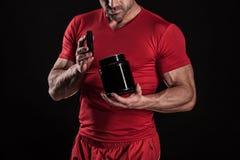 Hombre atlético joven hermoso que lleva a cabo un tarro de nutrición de los deportes imágenes de archivo libres de regalías