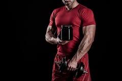 Hombre atlético joven hermoso que lleva a cabo un tarro de nutrición de los deportes imagenes de archivo